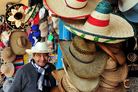 "fiesta popular: TEOTIHUCAN - FEB 26:Mexican man wears a sombrero selling sombreros and cowboys hats on February 26 2010 in Teotihuacan, Mexico.its name derived from the Spanish word sombra, meaning ""shade""."