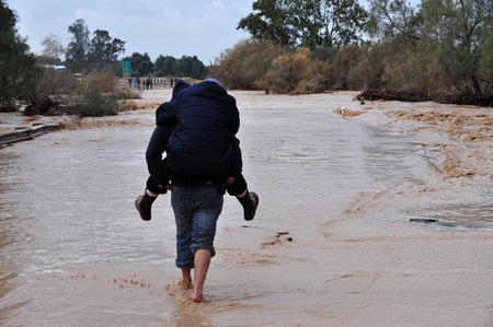 nahal: SOUTH ISRAEL - JANUARY 18: Travelers are trying to cross a flash flood in Nahal Habsor on January 18 2010 at the Western Negev, Israel.Flash floods in Israel are deadly people are killed by them each year