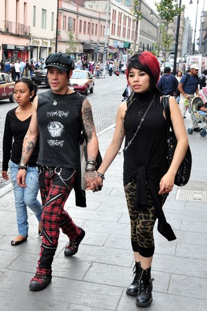informal clothes: MEXICO CITY - FEB 23:Punk couple hold hands on February 23 2010 in Mexico City, Mexico.Its a radical style using unconventional combinations of elements and materials with high shock value. Editorial