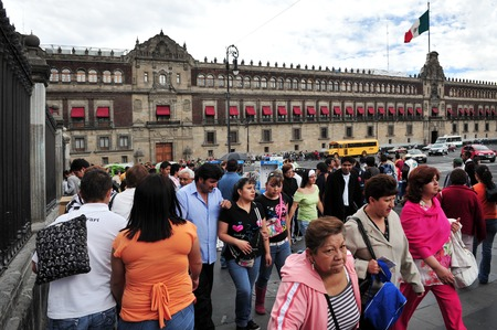 commissioned: MEXICO CITY - FEB 23:Mexicans outside the National Palace on February 23 2010 in Mexico City, Mexico.It commissioned and designed by Hernan Cortez, and is one of the oldest buildings in Mexico City.