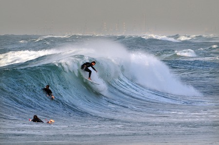 originated: ASHKELON - DEC 12: Wave surfer surfing wave at sea on December 12 2009 in Ashkelon, Israel.It originated by Polynesian people and was first discovered by Captain Cook in 1778. Editorial
