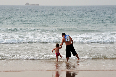 constituting: ASHDOD - NOV 07:Israeli father and son enjoy the sea on Nov 07 2009.The population of children living in Israel numbered ABOUT of 2,500,000 children, constituting over 30 of the general population.