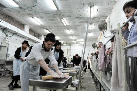 santa cena: Hombres jud�os ortodoxos son preparar matz� kosher glat hechos a mano en Kisse Rahamim Matzot f�brica en Moshav Brichia, el sur de Israel. Pascua es un d�a santo y la fiesta jud�a que conmemora la salida de Egipto y la liberaci�n de los israelitas de esclavo
