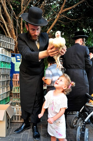 ashdod: ASHDOD - SEPTEMBER 15 : Ultra orthodox Jewish man waves a chicken over his daughter head during the Kaparot ceremony held on September 15 2010 in Ashdod Israel.