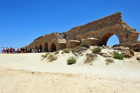 bce: CAESAREA - DEC 13:Visitors at the ancient Roman aqueduct at Ceasarea on Dec 13 2009. The ancient Caesarea Maritima city and harbor was built by Herod the Great about 25–13 BCE. Editorial
