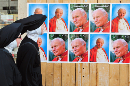 beatification: A Catholic nuns are looking at a giant banner bearing John Pauls portrait is unveiled over the facade of St Peters basilica during the ceremony of beatification for late pope John Paul II on May 1, 2011 at St Peters square at the Vatican city in Rome I Editorial