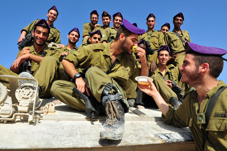 israelis: ZIKIM - SEPTEMBER 07: IDF soldiers are blessing on the traditional jewish custom of apple and honey to welcome Rosh Hasahanah, the Jewish New Year on September 07 2010 in Gaza border near Zikim, Israel.