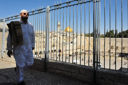 talmud: JERUSALEM - NOV 05:Muslim man passing by the Western Wall on November 05 2011 in Jerusalem, Israel.Its the most sacred site recognized by the Jewish faith outside of the Temple Mount itself.