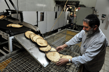 matzah: JERUSALEM -MARCH 16: Orthodox Jewish men prepare hand-made glat kosher matzah on March 16 2010 in Jerusalem, Israel.