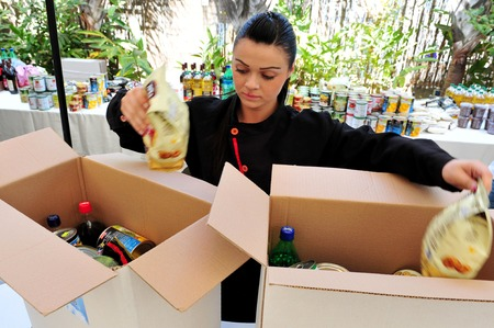 matzos: ASHDOD - APRIL 14: An Israeli woman prepares packages of food to give to the poor for the Jewish holiday of Passover in Ashdod, Israel on April 14, 2011. Passover is a Jewish holy day and festival. It commemorates the story of the Exodus in Egypt. It is o