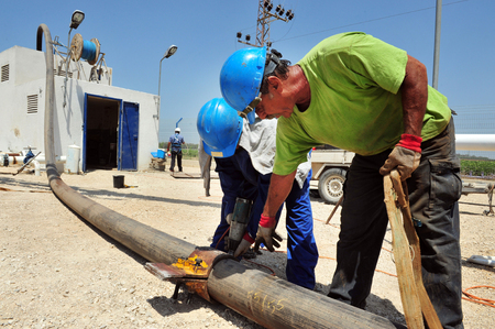 ASHKELON - AUGUST 05: Drilling engineers and workers maintaining water pipe for Mekorot the Israeli Water supply and sanitation company on August 05 2010 in Ashkelon, Israel.it supplies Israel with 90% of its drinking water and operates a cross-country wa Editorial