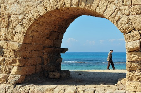 ceasarea: CAESAREA - DEC 13:Visitor at the ancient Roman aqueduct at Ceasarea on Dec 13 2009. The ancient Caesarea Maritima city and harbor was built by Herod the Great about 25–13 BCE. Editorial