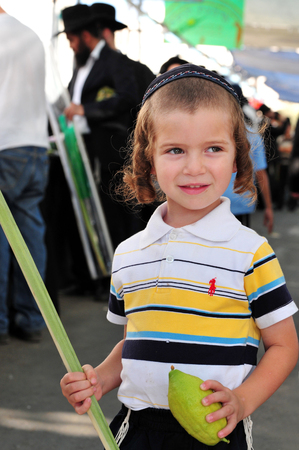 succos: ASHDOD - OCTOBER 12 : Jewish ultra-orthodox  child holds Etrog and Lulav at a four species market for the Jewish holiday of Sukkot on October 12 2011 in Ashdod,Israel.