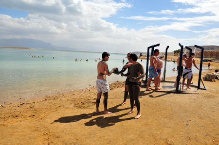 holyland: DEAD SEA, ISR - MAR 18:Young people in a bathing suit enjoys natural mineral mud on March  18 2010.The Dead Sea is filled with minerals including calcium, iodine, saline, potassium, and bromide. Editorial