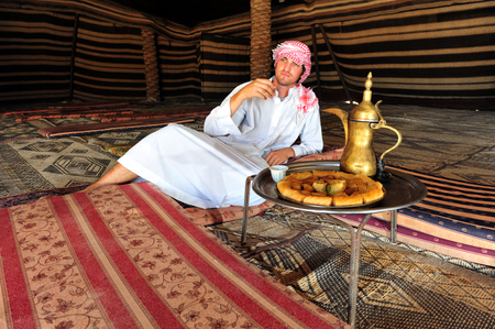 bedouin: WESTERN NEGEV - SEPTEMBER 10:A Bedouin man smokes hashsish, drinks turkish coffee and eats baklava in a traditional bedouin tent on Sep 10 2010.Negev Bedouin are formerly nomadic and later also semi-nomadic Arabs who live by rearing livestock in the deser
