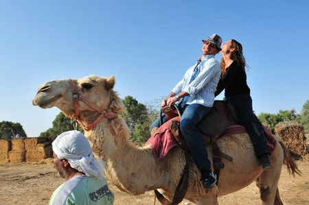 NEGEV, ISR - APR 07:Couple on a camel carry by Bedouin man on April 07 2011.The Negev covers more than half of Israel, over some 13,000 km² (4,700 sq mi) or at least 55% of the country's land area. Imagens - 46256421