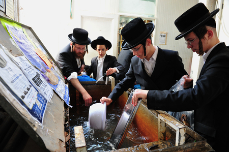 judaical: ASHDOD - APRIL 15: Ultra Orthodox Jewish men repare for the Jewish holiday of Passover on April 15 2011 in Ashdod, Israel.