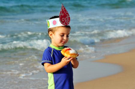 hanukka: ASHDOD - NOVEMBER 27: An Israeli boy eats a jam filled donut on the beach during the Jewish holiday of Hanukkah on November 27 2010 in Ashdod, Israel. Editorial