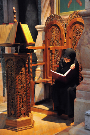testimony: JERUSALEM - NOVEMBER 05:Nun reads the New Testimony at the Church of the Holy Sepulchre November 05 2010 Jerusalem,Israel.The Holy Sepulchre church considered the holiest Christian site in the world