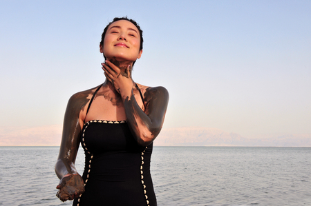 ein: DEAD SEA, ISR - MAY 14:Young Chines woman is enjoys natural mineral mud on May 14 2010.The Dead Sea is filled with minerals including calcium, iodine, saline, potassium, and bromide. Editorial