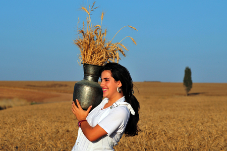 gat: KIRYAT GAT - MAY 24: Israeli girl in a wheat field celebrate the Jewish holiday Shavuot by carry the first wheat harvest in a pitcher on May 24 2009 near Kyryat Gat, Israel.Its Judaisms third largest feast which commemorates the handing down of the five