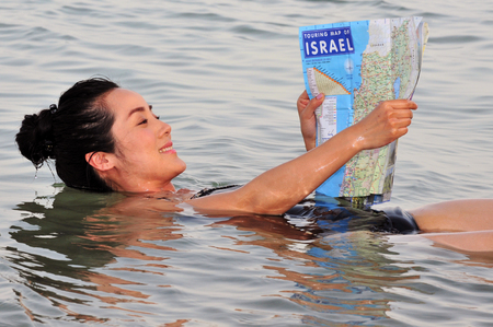 ein: DEAD SEA, ISR - MAY 14:A young Chinese woman floats while reading a map of Israel on May 14 2010.Its the second saltiest body of water in the world, with a salt content of 33% and that creates a natural buoyancy.