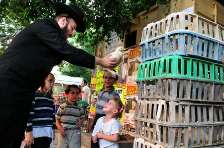 ashdod: ASHDOD - SEPTEMBER 15 :Ultra orthodox Jewish man waves a chicken over his children head during the Kaparot ceremony held on September 15 2010 in Ashdod Israel.
