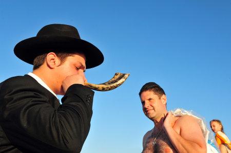 ASHDOD - SEPTEMBER 09: Jewish orthodox man Blows the shofar during the Jewish ceremony of Tashlich to begin the Jewish new year on September 9 2010 in Ashdod, Israel.