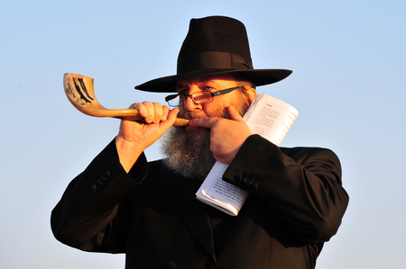 siddur: ASHDOD - SEPTEMBER 09: Jewish orthodox man Blows the shofar during the Jewish ceremony of Tashlich to begin the Jewish new year on September 9 2010 in Ashdod, Israel.
