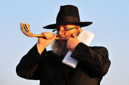 ashdod: ASHDOD - SEPTEMBER 09: Jewish orthodox man Blows the shofar during the Jewish ceremony of Tashlich to begin the Jewish new year on September 9 2010 in Ashdod, Israel.