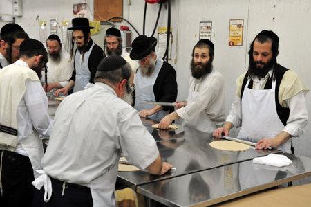 santa cena: Hombres judíos ortodoxos son preparar matzá kosher glat hechos a mano en Kisse Rahamim Matzot fábrica en Moshav Brichia, el sur de Israel. Pascua es un día santo y la fiesta judía que conmemora la salida de Egipto y la liberación de los israelitas de esclavo