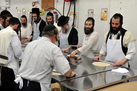 matzah: Orthodox Jewish men are prepare hand-made glat kosher matzah at Kisse Rahamim Matzot Factory in Moshav Brichia, southern Israel. Passover is a Jewish holy day and festival commemorating the Exodus from Egypt and the liberation of the Israelites from slave