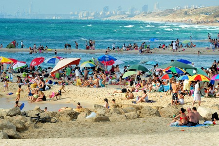 israelis: ASHKELON,ISR - JUNE 06:Visitors in Ashkelon beach on June 06 2011.Its southernmost city on the Israeli Mediterranean shoreline with 12 km of beautiful beaches attracts Israelis and foreign tourists.