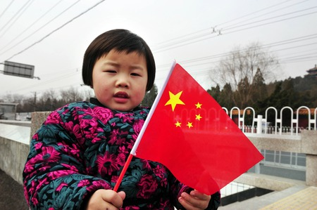 one child: BEIJING - MARCH 11:Chinese girl holds the flag of China on March 11 2009 in Beijing, China.When One Child Policy was adopted in 1979,Chinas population was about 972 million. Today its about 1.343 billion people. Editorial