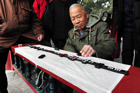 play popular: BEIJING-MARCH 15:Chinese people play domino at the Temple of Heaven park on Mar 15 2009 in Beijing, China.Its the most popular park in Beijing used by thousands of people for sport and leisure daily