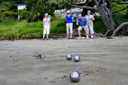 french boule: Old people playing boules on the beach.
