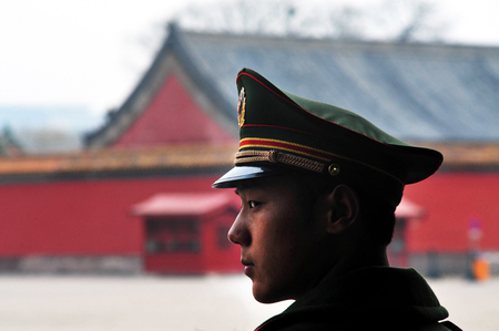 attain: BEIJING - MARCH 11:Chinese soldier guards inside the Forbidden City on March 11 2009 in Beijing,China.Military service in China is compulsory, in theory, for all men who attain the age of 18