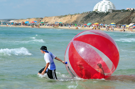 suffocation: ASHKELON - JUNE 18: Israeli childrens having fun inside a giant water walking ball in Ashkelon beach on June 10 2011.The sport have high risk of suffocation, drowning and Injury. Editorial