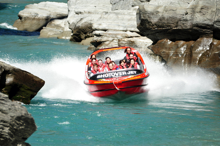 zealand: QUEENSTOWN,NZ - FEB 20: Tourists enjoy a high speed jet boat ride on the Shotover River on February 20, 2009 in Queenstown, New Zealand. Queenstown is one of the most popular summer resort in NZ.