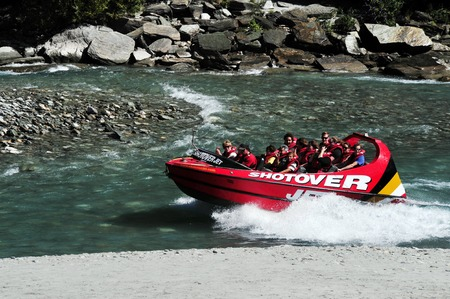 nz: QUEENSTOWN,NZ - FEB 20: Tourists enjoy a high speed jet boat ride on the Shotover River on February 20, 2009 in Queenstown, New Zealand. Queenstown is one of the most popular summer resort in NZ.