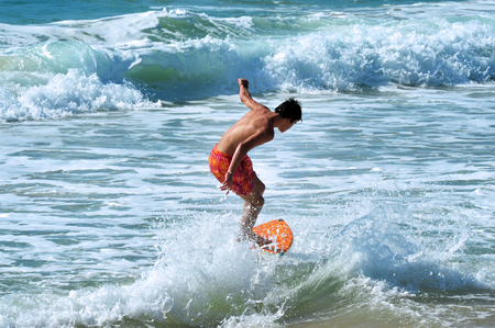 get across: ASHDOD - JUNE 26: A boy skimboarding on the beach on June 26 in Ashdod,Israel. Skimboarding originated in Southern California when lifeguards wanted an easy way to get across the beaches of Laguna.