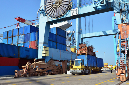 old container: A big container vessel in a container seaport during transportation of cargo in containers by cranes and lorry trucks. Editorial