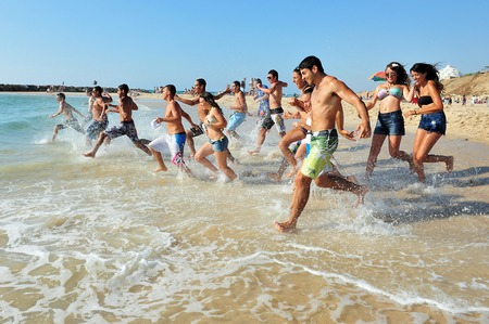 israel people: ASHKELON,ISR - JUNE 06:Israeli high school graduates runs to the sea on June 20 2011.According to the OECD The percentage of high school graduates in Israel is among the highest in the world, about 92