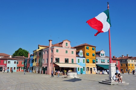 colorfully: Big Italian flag against a colorfully painted houses on Burano island in the Venetian Lagoon, northern Italy.