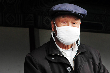 animal health: BEIJING-MARCH 15:Chinese man wear surgical masks on Mar 15 2009 in Beijing, China.In Asia its common to wear masks if person is sick in courtesy to prevent spreading their own infection to others.