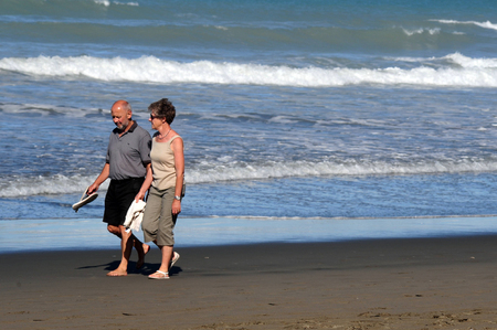 warning system: CHRISTCHURCH - FEB 25:Mature couple enjoy Sumner beach in Christchurch,NZ on Feb 25 2009.Tsunami warning system have been installed along Christchurch coastline after 2011 earthquake killed 185 people Editorial