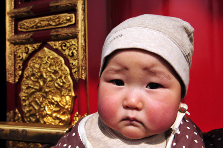 BEIJING - MARCH 11:Chinese baby at the Forbidden City on Mar 11 2009 Beijing, China. When One Child Policy was adopted in 1979,Chinas population was about 972 million. Today its about 1.343 billion people. 新聞圖片