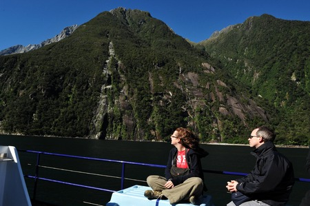 explores: FIORDLAND, NZ- FEB 28:Tourist explores Milford Sound on February 28 2009.Its one of the most  beautiful parts of New Zealand and the largest of NZ national parks with an area of 12,500 km.