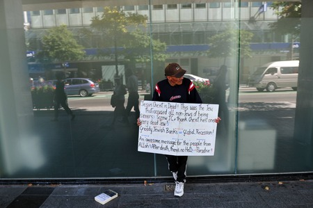 criticized: CHRISTCHURCH - FEB 29:Muslim man holds Anti Semitic sign outside a bank in Christchurch on Feb 29 2009,NZ.The 20082012 global recession is shaping up to be the worst post-World War II great recession
