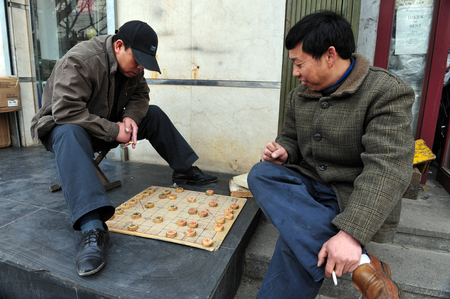play popular: BEIJING - MAR 14:Chinese people play Xiangqi Chinese Chess in Beijing,China on March 14 2009.Its one of the most popular board game in the world, played by millions of people in China and Asia. Editorial